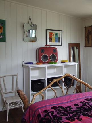 The bed is made from found branches and the old suitcase jukebox was purchased in Melbourne.